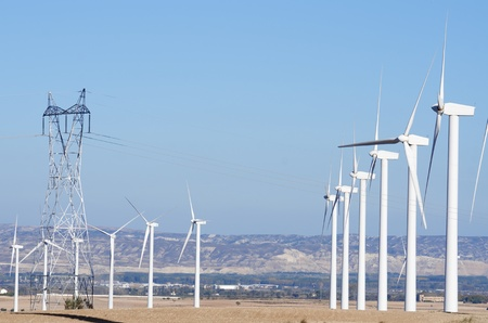 group of  windmills for electric power  production and high voltage tower photo