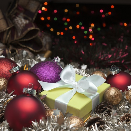 yellow box tied with a white ribbon and christmas decoration Stock Photo