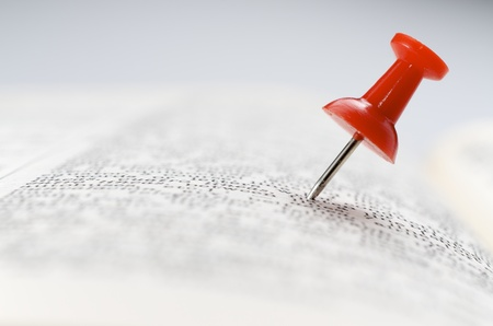 Close up of a red thumbtack  stuck in a book photo