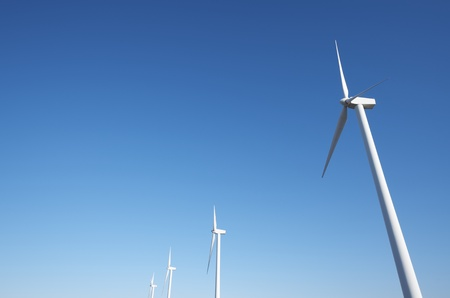 aligned windmills for renowable electric production with blue sky photo