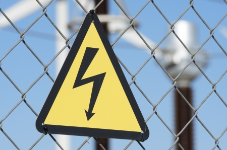 electrical hazard sign placed on a metal fence photo