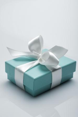 gifts: kleine turquoise doos gebonden met een wit lint Redactioneel