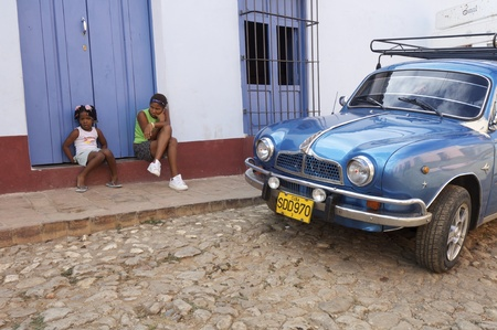 Trinidad, Cuba - February 2, 2007: girls  sitting on the street and old blue car in one of  the main streets of Trinidad