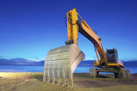 gravel pit: view of a yellow backhoe  on a beach at sunrise