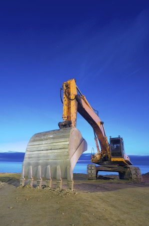 view of a yellow backhoe  on a beach at sunrise photo