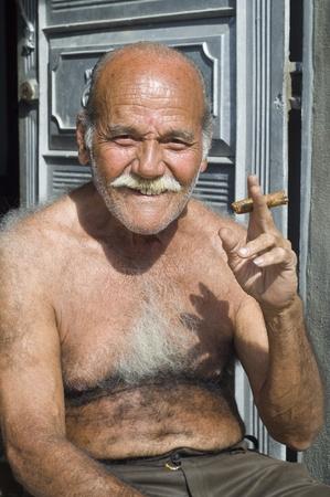 amabilidad: La Habana, Cuba - 31 de enero de 2007: Un cubano se sienta a la puerta de su casa de acogida con un cigarro en la mano. Cuba es famosa de sus cigarros y la amabilidad de sus habitantes.