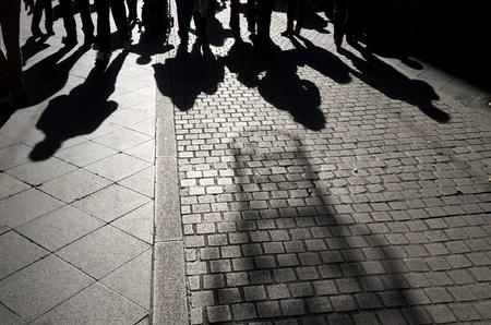 Schatten von Menschen zu Fuß entlang einer gepflasterten Straße, Sevilla, Andalusien, Spanien