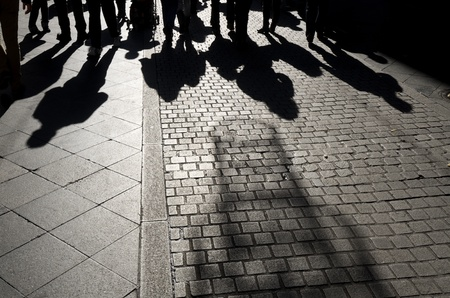 footpath: shadows of people walking along a  cobblestone street, Seville,  Andalucia, Spain