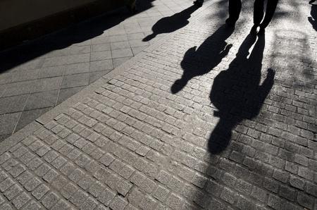Schatten von Menschen zu Fuß entlang einer Straße mit Kopfsteinpflaster, Sevilla, Andalusien, Spanien