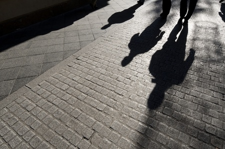 black shadow: shadows of people walking along a  cobblestone street, Seville,  Andalucia, Spain
