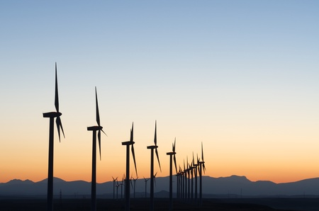 aligned windmills for renowable electric production at sunset Stock Photo
