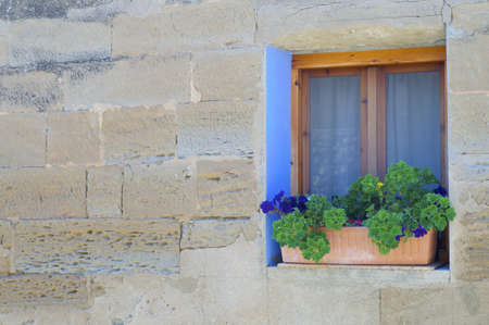 supported  pots in the window of  an old stone house in Spain photo
