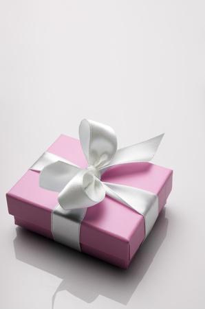 madre soltera: peque�a caja de color rosa atado con una cinta blanca Foto de archivo
