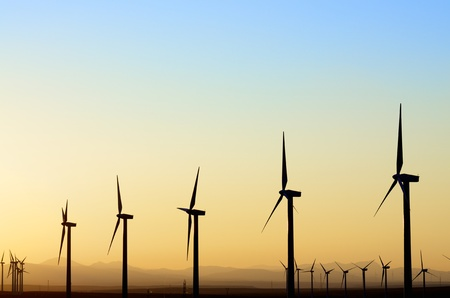 windfarm: aligned windmills for renowable electric production at sunset Stock Photo