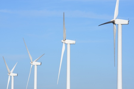 aligned group of windmills for electric power production photo