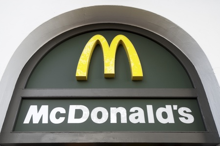 Seville,  Spain - December 28, 2011:  sign at the entrance of  a restaurant. McDonald's is the fast food restaurant in the world. To show its responsibility  to natural resources, at present, the logo is green and yellow.