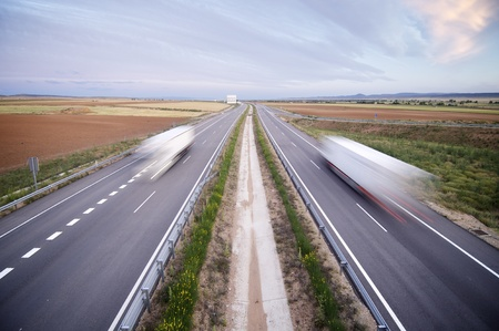 trucks traveling along a straight highway photo
