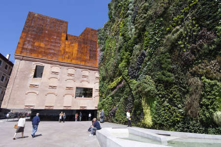 botanist: Madrid,  Spain - June 7, 2008: entrance to the Caixa Forum building, this building is dedicated to artistic exhibitions varied. The facade is the work of plant botanist Patrick Blanc
