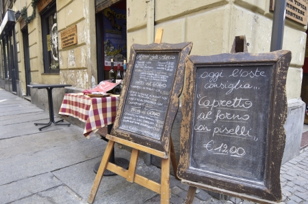 Turin, Italy - April 8, 2009: blackboards announcing the typical menus that taste the thousands of tourists visiting daily the old city