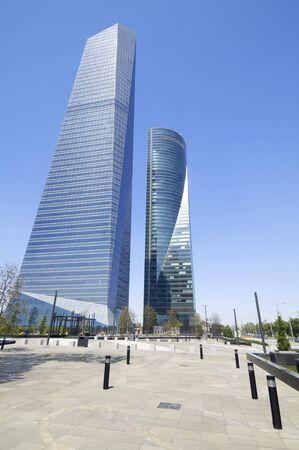 Madrid, Spain - July 29, 2009: Cuatro Torres Business Area next to the Paseo de la Castellana. To the left of the Glass Tower designed by architect Cesar Pelli Tower and right Space Tower designed by architect Henry N. Cobb.