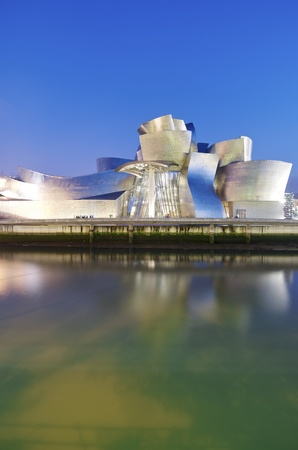 Bilbao, Spain - July 30, 2011: night view of the  Guggenheim Museum and Nervion river at sunset. Guggenheim Museum is dedicated  exhibition of modern art and was  designed by architect Frank Gehry.