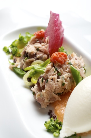 forefront of  an appetizer of tuna, tomato  and vegetables photo