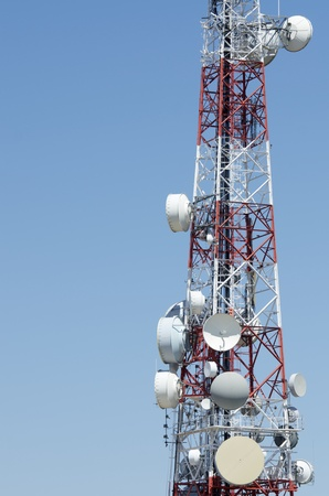 closeup of  a telecommunications tower with a clear blue sky photo