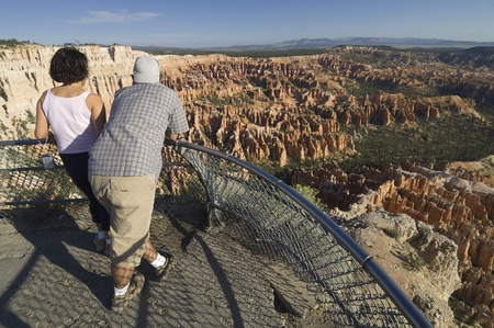Bryce Canyon, USA - August 26, 2007, two park visitors contemplate the landscape. Throughout the park there are several vantage points near the road that are visited by thousands of tourists every year.