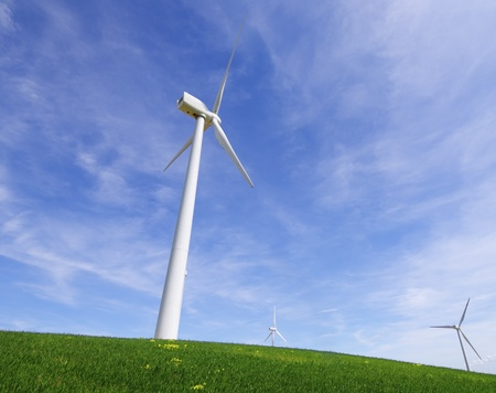 windmills in a green meadow with blue sky photo