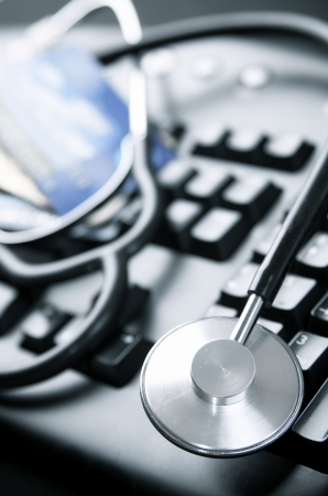 close up of a stethoscope and a computer keyboard with credit cards photo