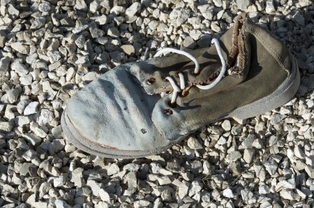 forefront of a sneaker old abandoned on a gravel floor photo