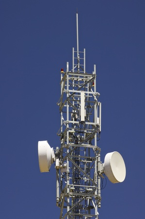 bottom view of  a telecommunications tower with a clear blue sky photo