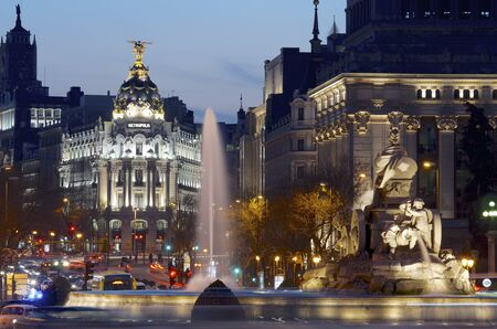 Madrid, Spain - March 22, 2012: heavy traffic in the historic center of Madrid, highlights the Metropolis building and the Cibeles fountain, two of the most visited monuments in the city.