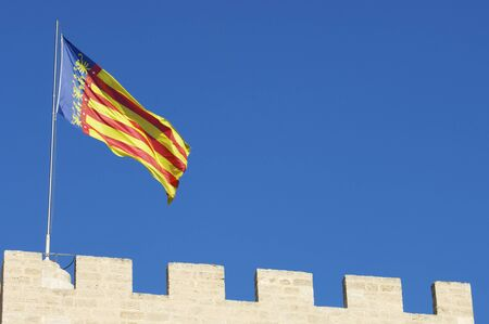 autonomic: forefront of the flag of Comunidad de Valencia in one of the towers of the old city, Valencia, Spain Stock Photo