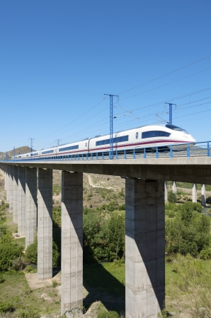 view of a high-speed train crossing a viaduct in Castejon de las Armas, Saragossa, Aragon, Spain; AVE Madrid Barcelona Editorial