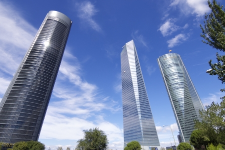 castellana: Madrid, Spain - September 24, 2010: Cuatro Torres Business Area next to the Paseo de la Castellana. To the left PwC Tower, designed by architects Rubio Carvajal and Alvarez-Sala, in the center the Glass Tower designed by architect Cesar Pelli Tower and ri
