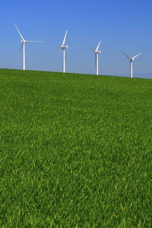 windmills in a green meadow with blue sky in Pozuelo de Aragon, Saragossa, Spain photo