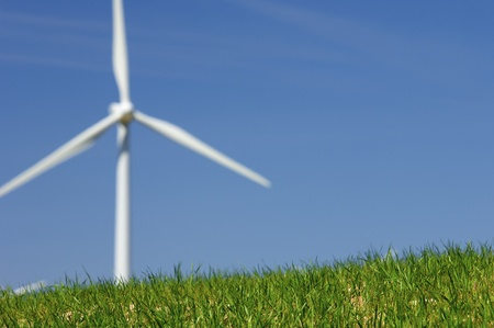 windmill for renewable energy production in a meadow of fresh grass photo
