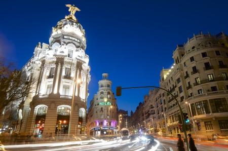 edificación: Madrid, Espa�a - 22 de marzo de 2012: el tr�fico en la calle conocida como la Gran V�a, una de las calles m�s concurridas de la ciudad y viaj� a diario por miles de turistas. Desde los edificios se encuentra el edificio conocido como Metropolis.