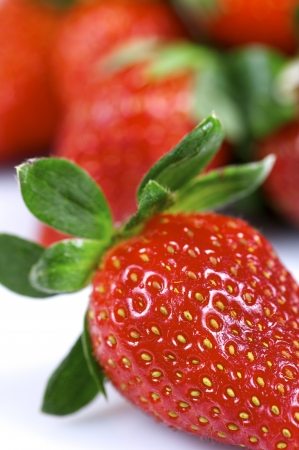 forefront: forefront of a group of fresh strawberries on a white background