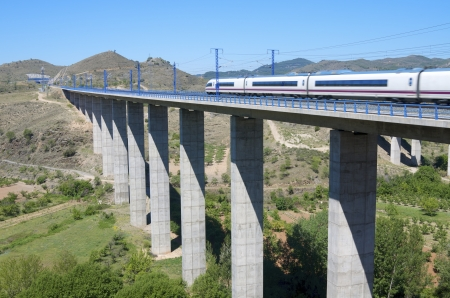 view of a high-speed train crossing a viaduct in Castejon de las Armas, Saragossa, Aragon, Spain; AVE Madrid Barcelona Stock Photo