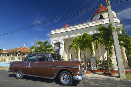 Cienfuegos, Cuba - February 1, 2007: view of a typical Cuban car parked on the street, with decades old, these vehicles are still used. A woman rests on the porch.