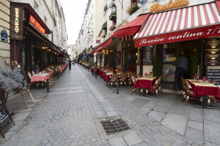 the place is outdoor: Paris, France - October 10, 2011: Tourists walking down a typical street with cafes and restaurants.