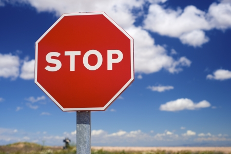 Stop sign and blue sky with white clouds photo