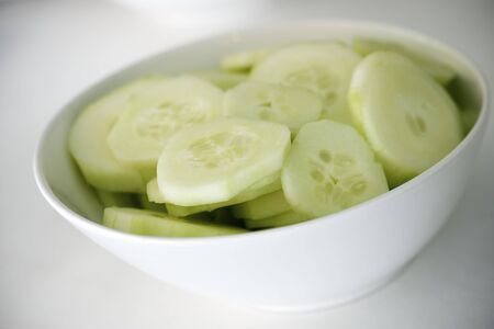 closeup of a white porcelain bowl with cucumber slices photo