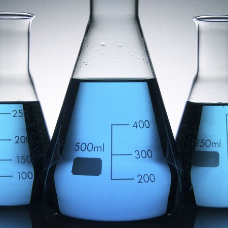 laboratory flasks with blue liquid inside