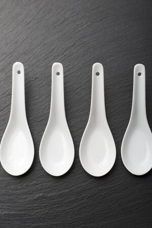 four small white spoons on a table slate photo
