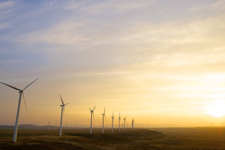 Windmills for electric power production at sunset, Pozuelo de Aragon, Zaragoza, Aragon, Spain photo