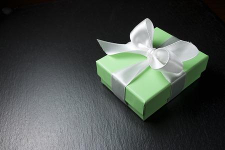 shiny black: Luxury box tied with a white ribbon. Stock Photo