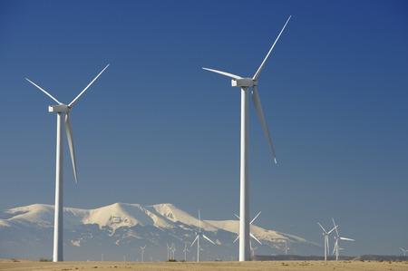 Windmills for renewable electric energy production, at background is Moncayo Peak, Pozuelo de Aragon, Zaragoza, Aragon, Spain photo